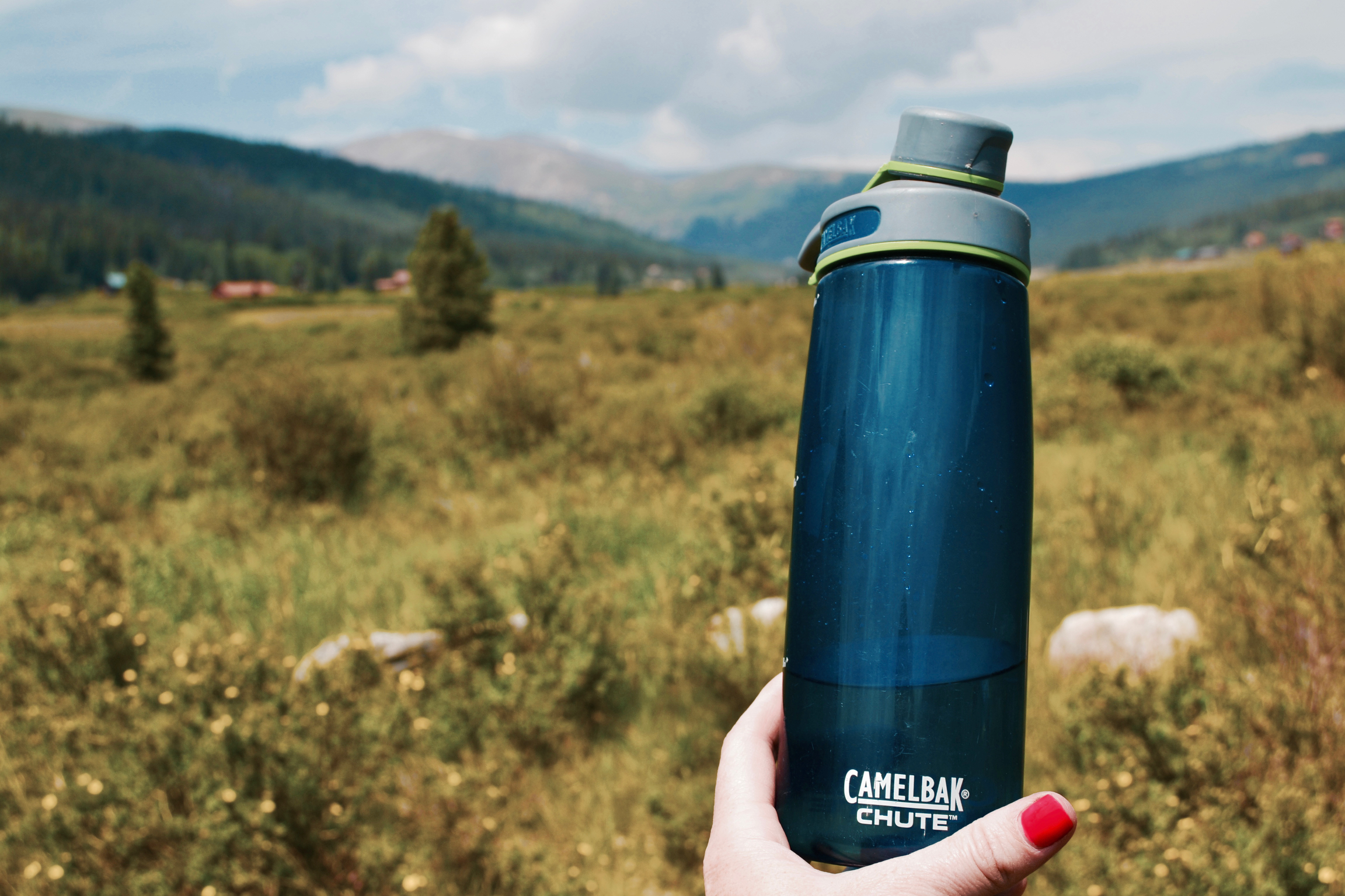 A Camelbak Chute water bottle held up in front of a beautiful mountain scene.