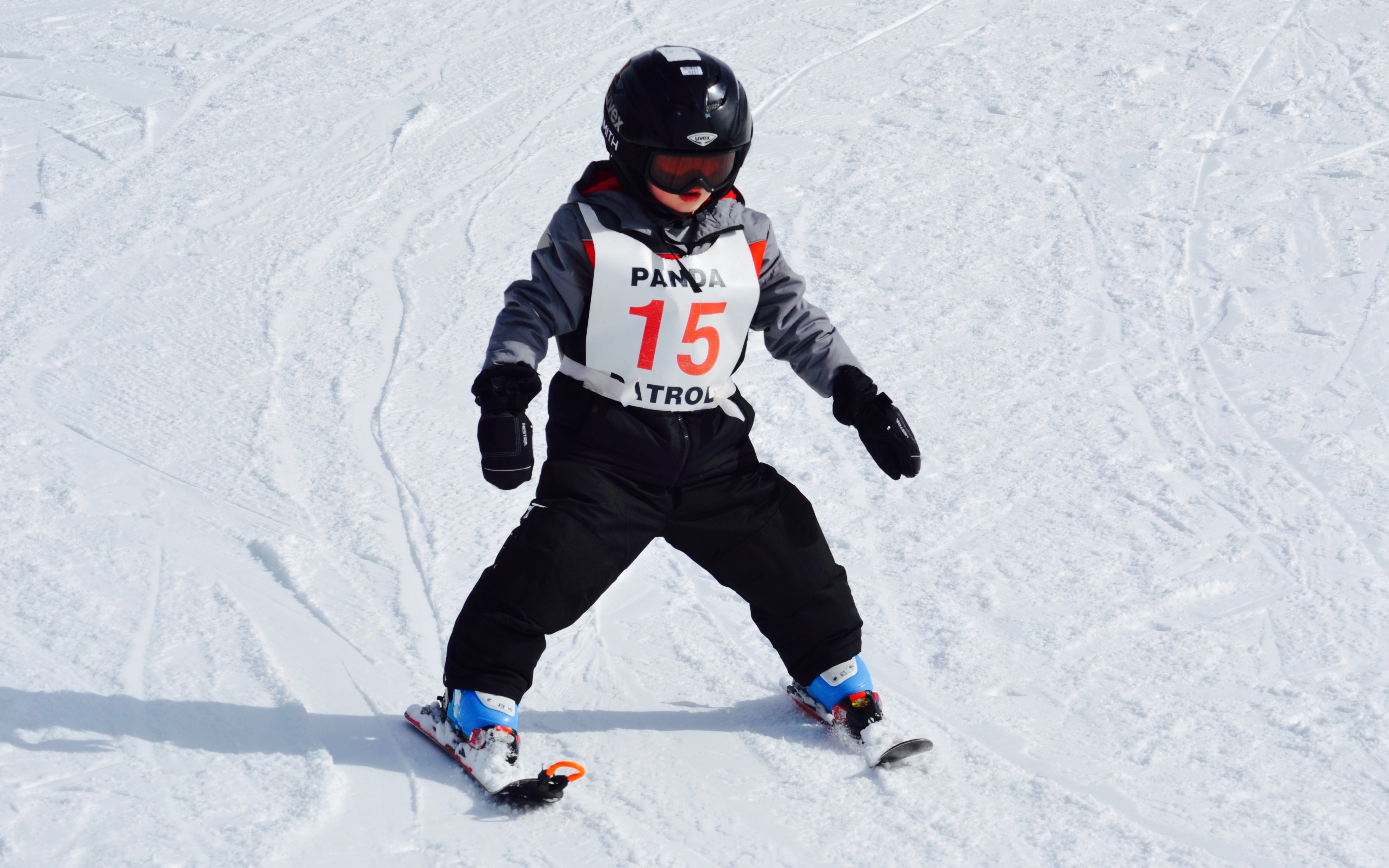 A toddler skiing for the first time down a slope covered in white snow.