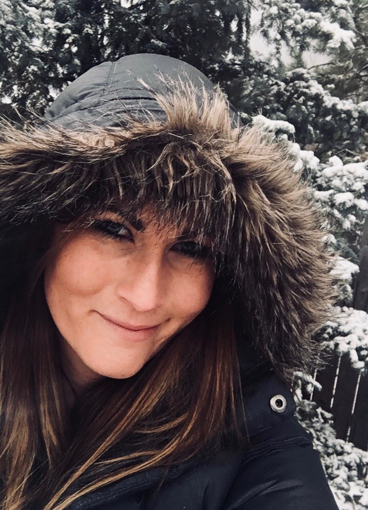 A woman blogger with a fur hood on her coat standing outside in the snow smiling.