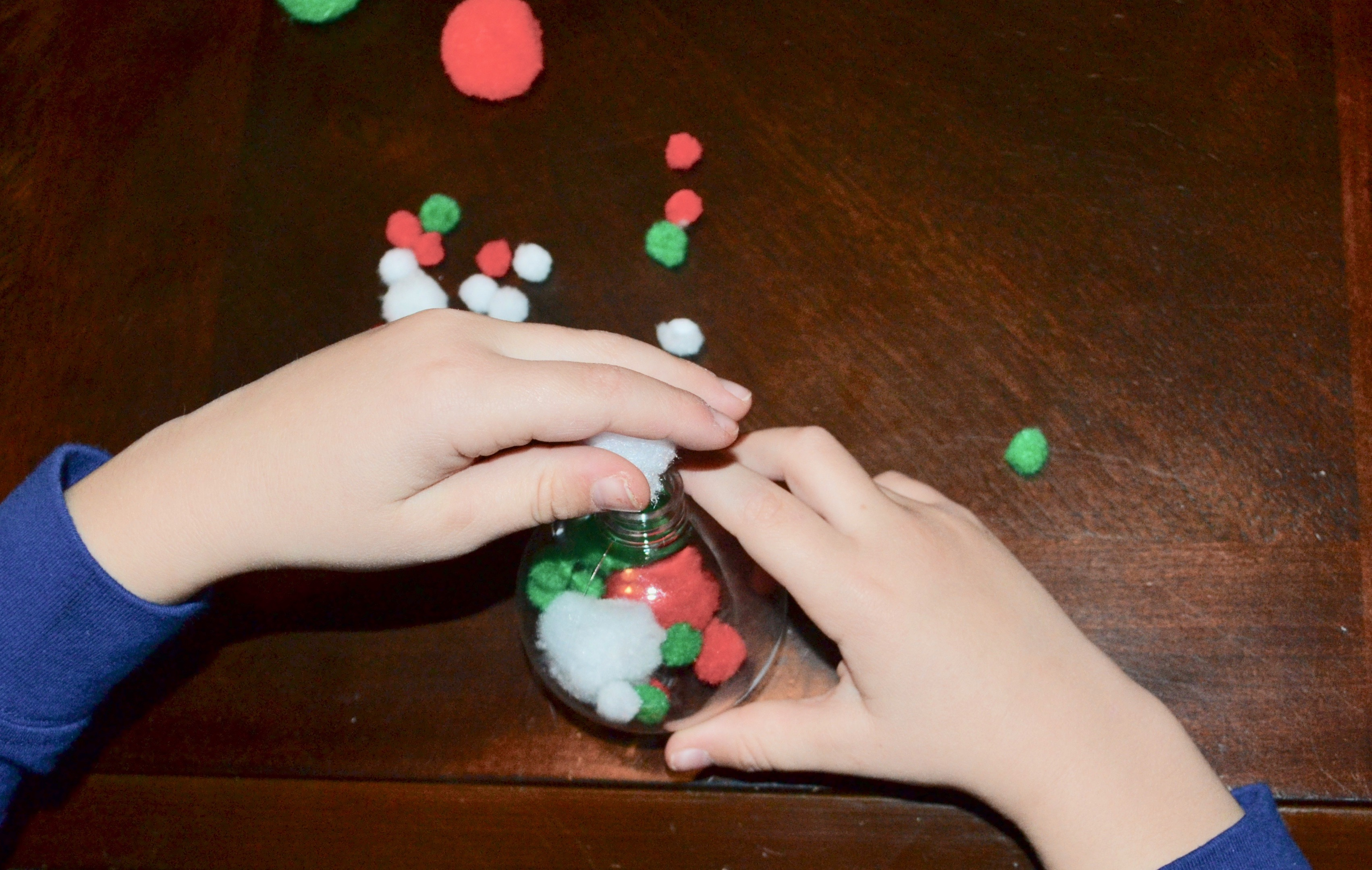 One little elf filling his Christmas ornament with red, green, and white pom poms.