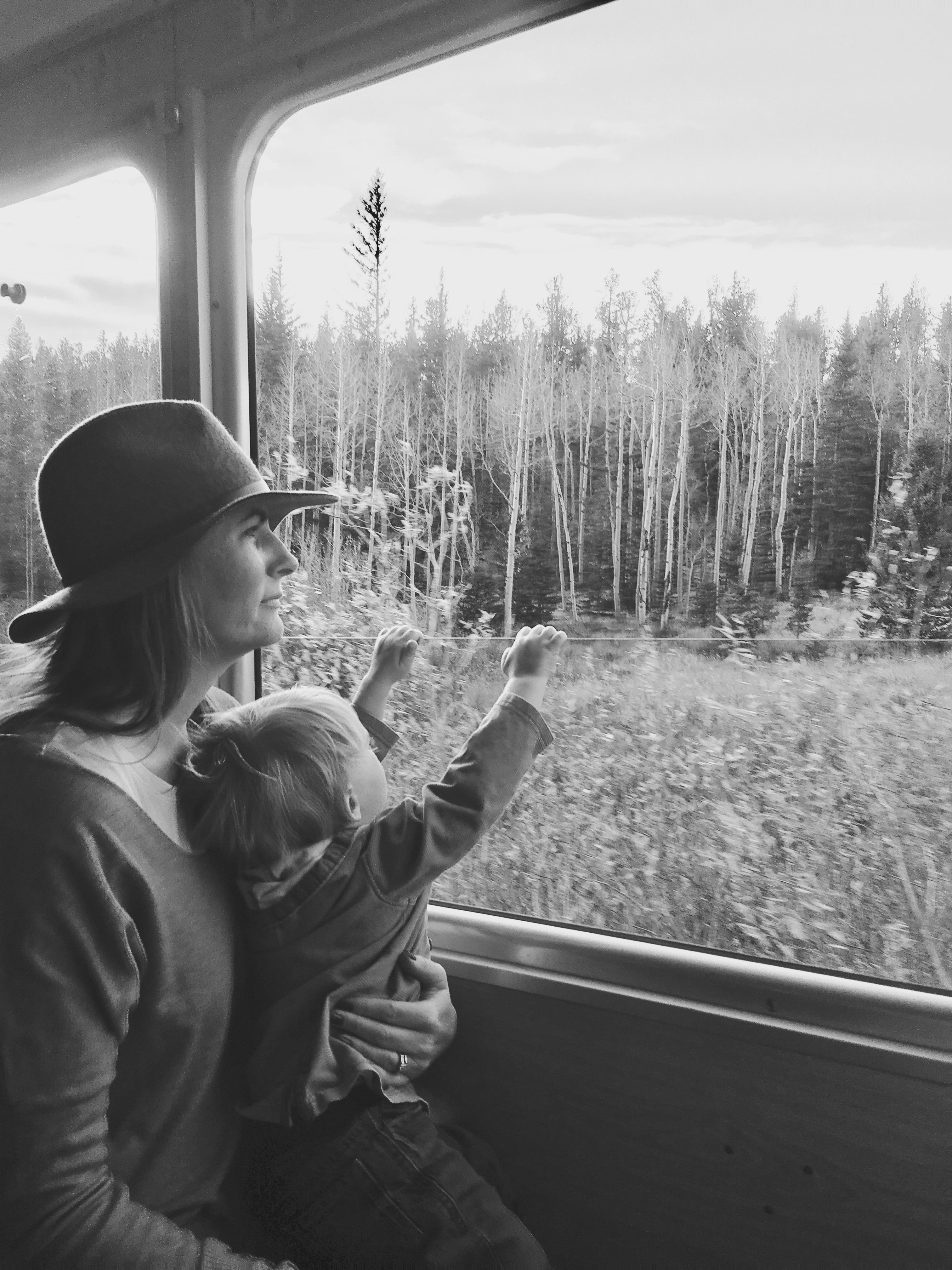 A mother and her son look out the window in the mountains. Top 10 ways to boost your mom mood during the winter months. whitswildtribe.com